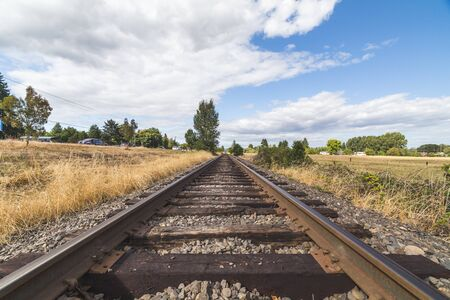 northwest: Wood and steel tracks under a deep blue sky with white clouds.