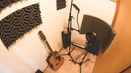 Guitar, microphones, and audio treatment panels in a recording studio room.