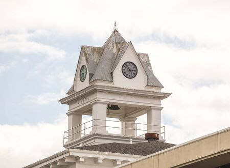 Clock Tower on top of a building on a bright summer day. Stock Photo