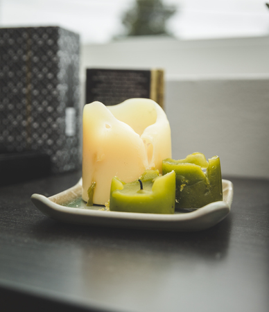 Large white candle and two smaller green candles on a plate on a shelf. Banco de Imagens