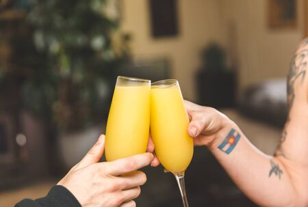 Two people tapping their beverages together for a cheers moment. Two drinks with orange juice and champagne, also known nas a mimosa.