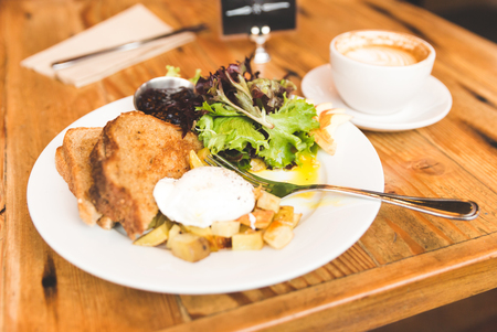 Eggs, potatoes, lettuce, toast and coffee in a breakfast meal spread. Upscale cafe setting.