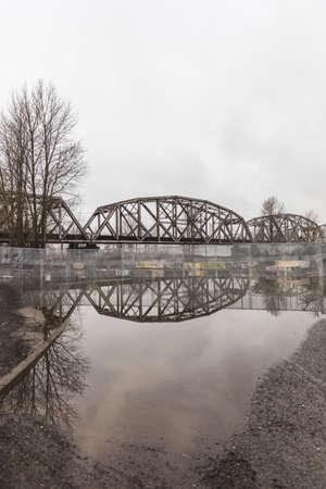 northwest: Railway bridge mirrored by reflective water on the ground in Portland, Oregon, USA.