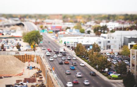 夏や秋の日にアメリカのアイダホ州ボイジーのティルト レンズ ショット。建設ゾーンとダウンタウンのビルの間に主要な道路上のトラフィックの車 写真素材
