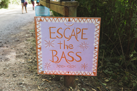 Sign reading Escape the BASS posted on a path near the stage of an outdoor music festival. Reklamní fotografie