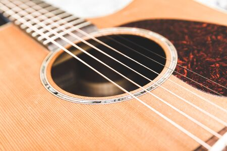 upscale: Closeup of steel strings and soundhole on an upscale acoustic guitar.