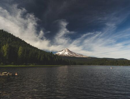 Summer day at Trillium Lake in Oregon, USA. Beautiful lake setting with forest, mountains, clouds, and blue sky. Stock Photo