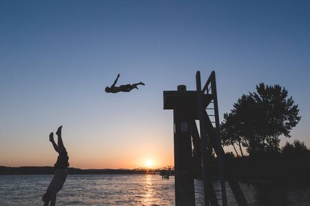 Two men dive from a platform into a large river at sunset. The Columbia River in Vancouver, Washington, USA.