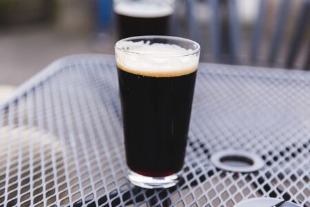 Pint glass full of a dark stout or porter beer. Outdoor patio setting.