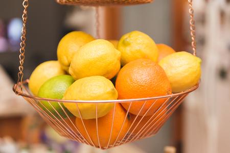 Lemons, oranges, and limes in a hanging metal basket inside a kitchen.