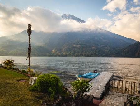Scene of Lake Atitlan in Guatemala of a small boat at a dock off of a backyard with a large mountain in the background shrouded in clouds and mist.
