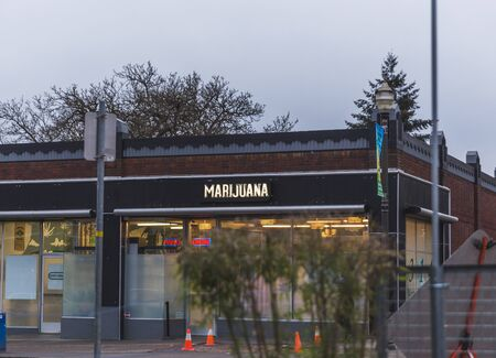 "Building with ""Marijuana"" on side of building in downtown city district."
