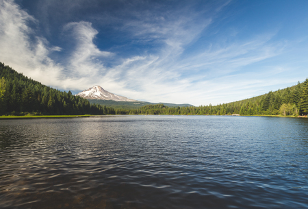 Scenic view of a mountain in the distance with a forest surrounding a lake in the foreground.