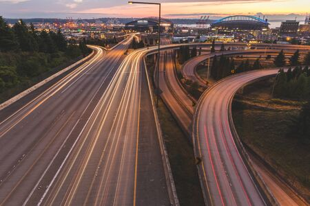 Long exposure shot of the highway near downtown Seattle, Washington in the evening sunset with stadium, arena and docks in the background. Editorial