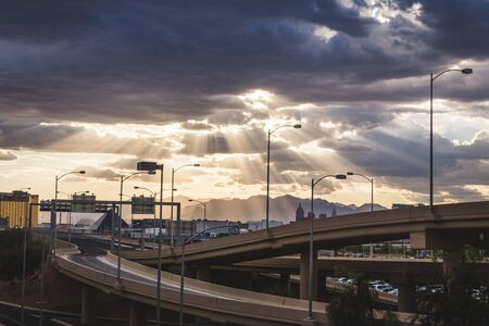 Sun rays shining through a cloudy sky over a superhighway scene in the city of Las Vegas.