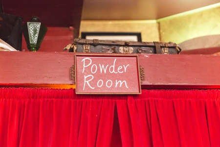 bathroom mirror: Powder Room words on sign over red curtains.
