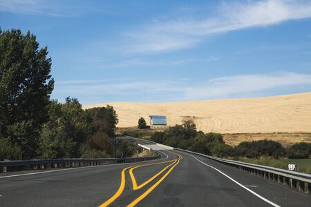 Barn building on farmland in rural countryside. Drivers point of view on highway. Stock Photo