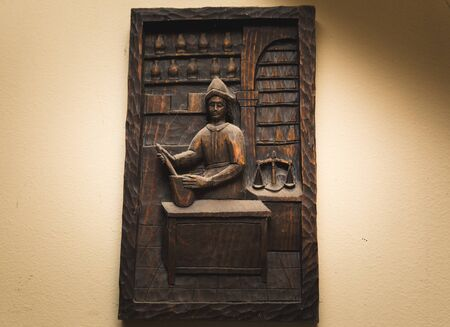 Wooden art piece with Spanish-looking merchant man or shopkeeper in a store or market setting.