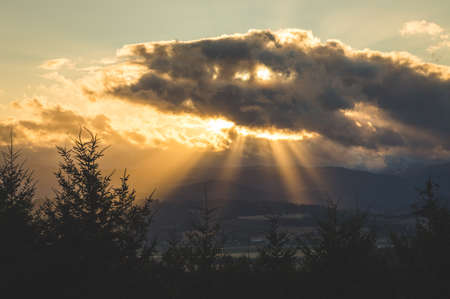 Clouds hovering in front of the sun in late afternoon allowing sun rays to shine through over a hilly forest landscape.