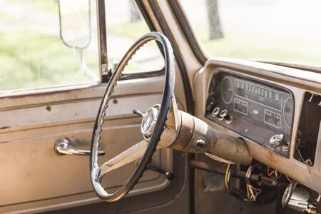 Steering wheel and gauge cluster inside the cabin of a classic pickup truck.