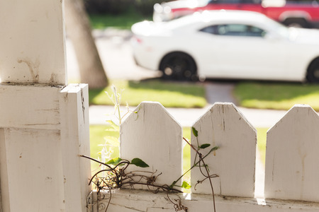 Residential white picket fence and gate near parked vehicles on street. Stock Photo