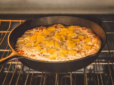 Homemade pizza with cheese and pineapple chunks baking on an oven rack in a cast iron pan. Banco de Imagens
