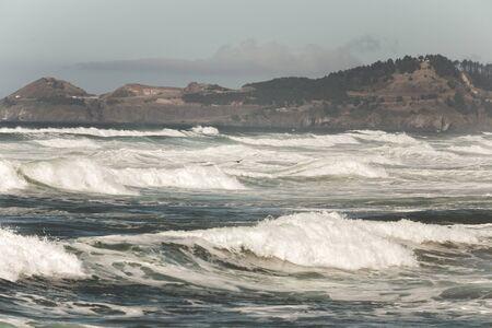 Rough surf at a rocky coastline on a hazy day.