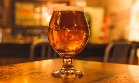 Golden colored beer in a curved glass on the counter of a bar.