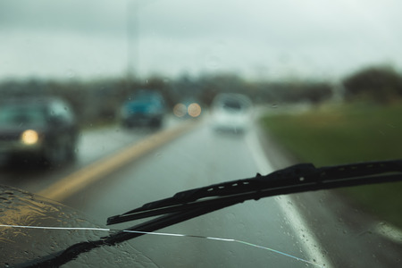 Windshield wiper and long crack on a windshield. Cars on road in background.