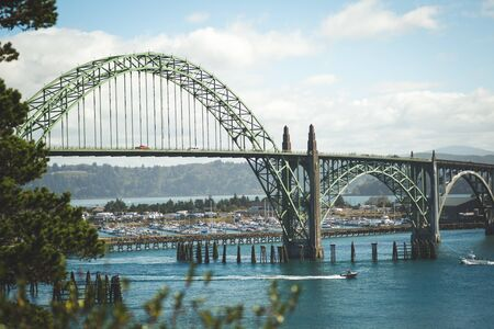 Suspended cable arch bridge over a river in the Pacific Northwest.