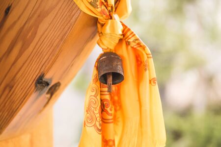 Bell with yellow and orange curtain or tapestry hanging from wooden structure.