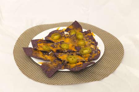tortilla de maiz: Placa de tortilla de maíz azul cubierta de queso con jalapeños.