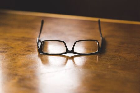 A pair of black eye glasses sitting alone on a brown wooden table top.