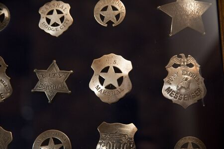 Collection of vintage or antique police badges inside a glass case.