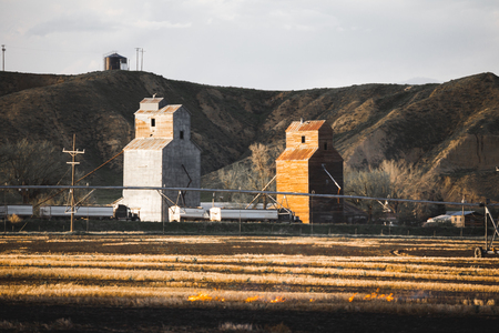 Crops burn in front of grainery buildings and equipment on a large farm.