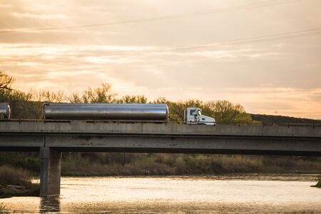 Semi truck with tanker trailers driving on a bridge over a river.