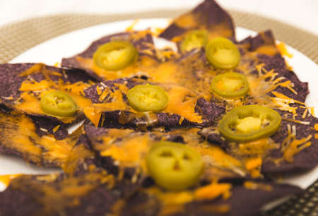 Plate of cheese-covered blue corn tortilla chips with jalapenos. Stock Photo