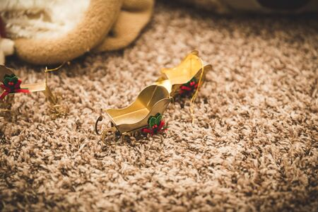Gold-colored Christmas sleigh ornaments on carpet.
