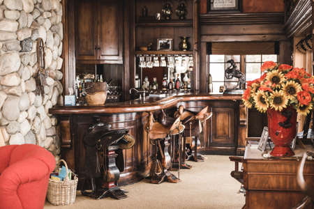 upscale: Custom made wood bar with saddle seats and various decorations inside a lavish cabin. Editorial