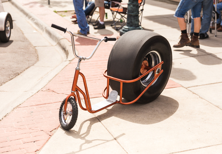Small scooter with a drag car rear tire.