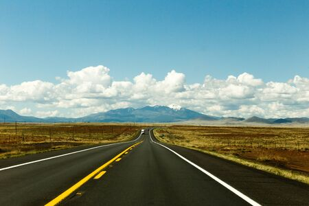 flagstaff: Highway landscape with blue sky, clouds, and mountains near Flagstaff, Arizona, USA.