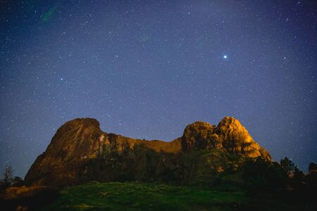 Stars over a large rock formation in western Montana, USA. Фото со стока