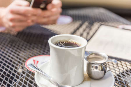 Fresh cup of coffee in glass mug next to creamer in metal serving cup. Person using phone in background.