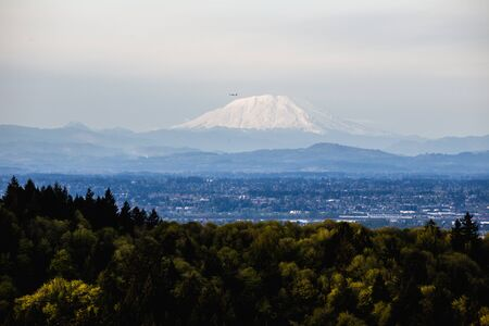 st: A commercial airline plane flies near the top of Mount St. Helens on a summer day. Seen from Portland, Oregon, USA.