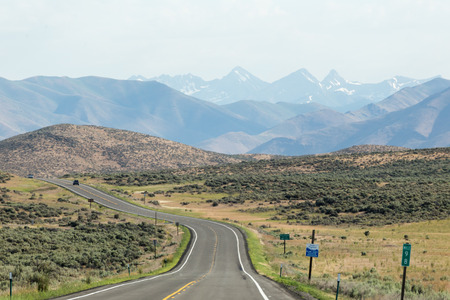 Empty desert highway with mountains in background. Southern Idaho, USA. Фото со стока - 83354805