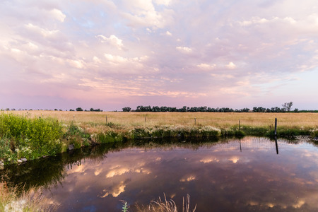 Still pond water reflecting the sky during a cloudy sunset or sunrise in rural farm landscape. Stock Photo