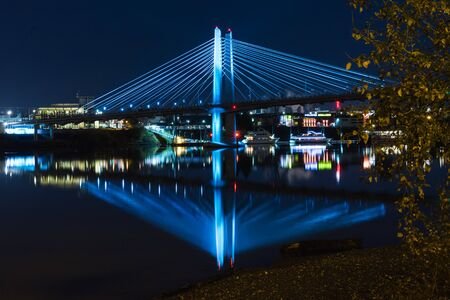 Tilikum Crossing at night in Portland. Lights shining on bridge with reflecting water below. Stock Photo