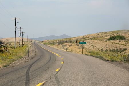 Empty eastern Oregon road with road sign for Huntington. Stock Photo