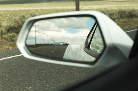 Reflection of side mirror on a sports car driving down remote highway. Spring or summer setting. Stock Photo