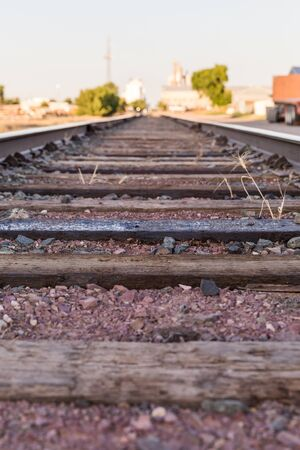 Details of railroad ties and ground. Train tracks in the industrial district of a town.